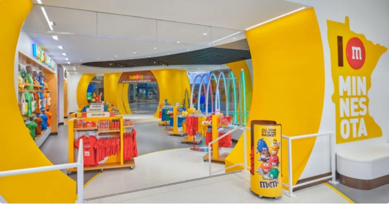 """Despite talk of shopping malls fading away as people turn to the internet to purchase goods and services, M&M's is investing in the future of physical retail. Earlier this month, the 80-year-old Mars brand opened a store in Minnesota's Mall of America, the nation's largest shopping complex. Filled with T-shirts, pillows, pajamas and socks, the 24,000-square-foot space contains nearly 3,000 SKUs and employs around 75 people. The second floor features a wall of clear tubes filled with approximately 8,000 pounds of M&M's candy. This is M&M's sixth store. Its other outlets operate in Orlando, Fla., Las Vegas, New York, London and Shanghai. The brand plans to open another store in Berlin later this year. So, why Mall of America? Because of geographical location, explained Patrick McIntyre, director of global retail at Mars Retail Group. """"We were really missing the middle of the country,"""" McIntyre told Adweek, noting the company already has a brick-and-mortar presence near the nation's two coasts. """"I think the biggest brands create the best moments in the biggest places, and there's nothing bigger than Mall of America,"""" he added."""